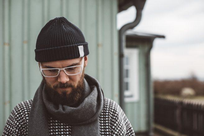 Mann med lue og briller ser ned, står utenfor husvegg.