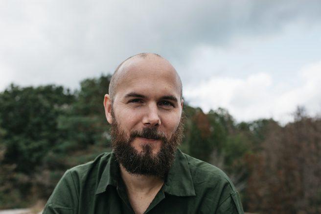 Mann med skjegg ser i kamera med skog i bakgrunn.