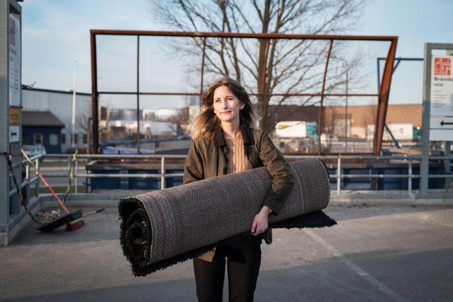 Kvinne bærer stort teppe på søppeldynga