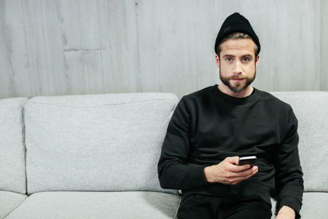 Ung mann sitter i sofa med mobil i handa og svart lue