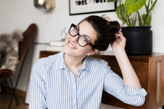 Dame med briller og skjorte smiler til kamera