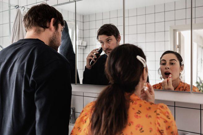 Mann barber seg og dame tar på leppestift i speilet på badet
