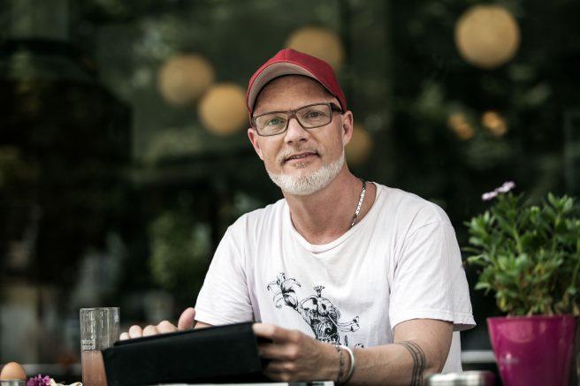Mann med rød caps og briller sitter ute med nettbrett