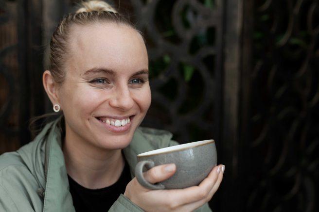 Ung kvinne smiler med kaffekopp